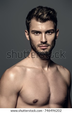 Portrait of a sexy young man with muscular body posing at studio. Gray background. Men's health. #746496202