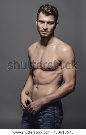 Portrait of a sexy young man with muscular body posing at studio. Gray background. Men's health. #750613675