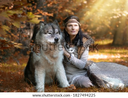 Portrait of a shaman woman with an Alaskan Malamute dog in the sunny forest