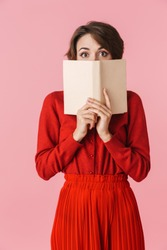 Portrait of a shocked beautiful young woman wearing red dress standing isolated over pink background, reading a book