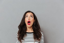 Portrait of a shocked girl looking up at copy space with open mouth isolated over gray background