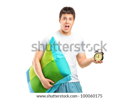 Portrait of a shocked male holding a pillow and alarm clock isolated on white background