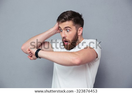 Portrait of a shocked man looking on wrist watch over gray background Stockfoto ©