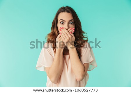 Photo of  Portrait of a shocked young girl in dress looking at camera with mouth covered isolated over blue background