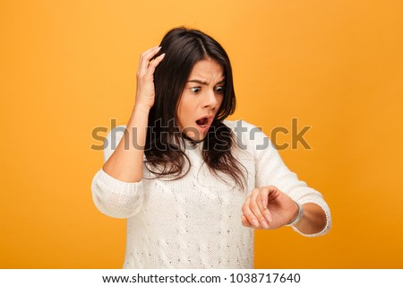Portrait of a shocked young woman looking at her wrist watch isolated over yellow background