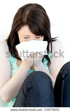 Portrait of a sick brunette woman blowing sitting on a sofa