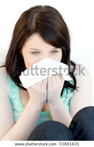 Portrait of a sick charming woman blowing sitting on a sofa - stock photo