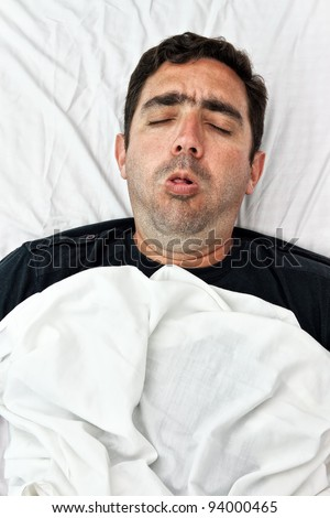 Portrait of a sick hispanic man laying in bed and coughing