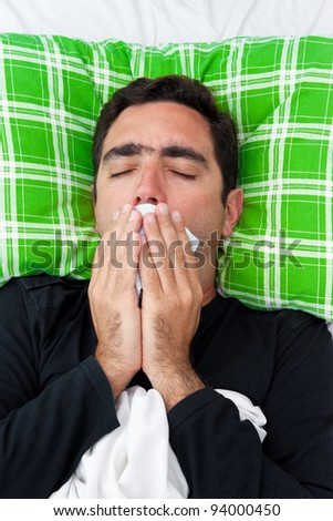 Portrait of a sick hispanic man laying in bed covering his mouth to avoid coughing or vomiting