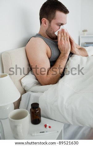Portrait of a sick man blowing his nose in his bedroom