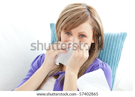 Portrait of a sick pretty woman blowing lying on a sofa against white background - stock photo