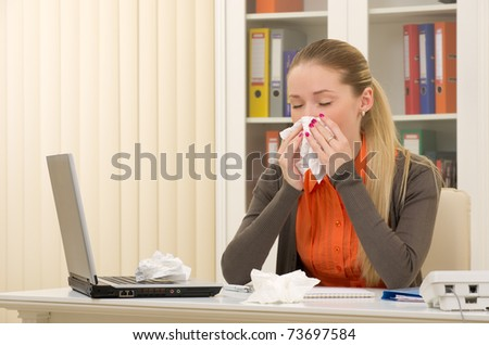 Portrait of a sick young business woman blowing her nose on her workplace