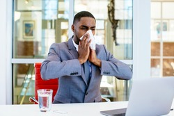 Portrait of a sick young man in business suit blowing his nose while sitting behind desk at work with computer