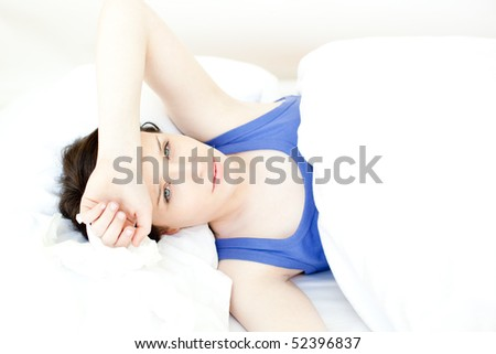 Portrait of a sick young woman lying on her bed at home