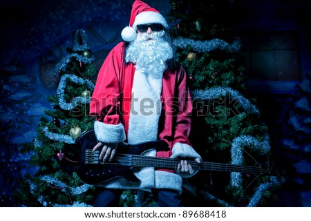 Portrait of a singing Santa Claus with electric guitar. Christmas.