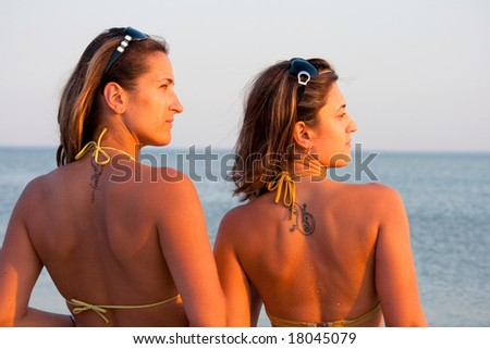 stock photo : portrait of a sisters with tattoos on their backs