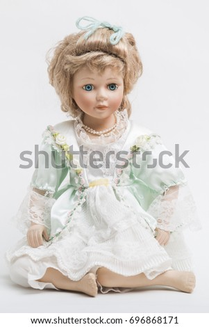 Portrait of a sitting ceramic porcelain handmade vintage doll with long blond hair and elegant hairstyle in an old linen dress with floral decorative embroidery on white background.