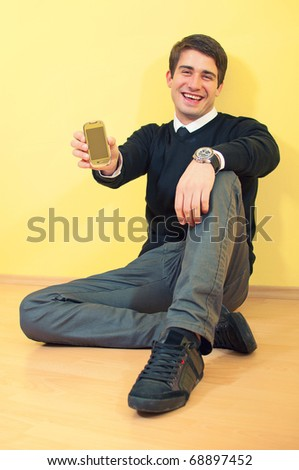 Portrait of a sitting smiling attractive young business man holding mobile phone against uniform background