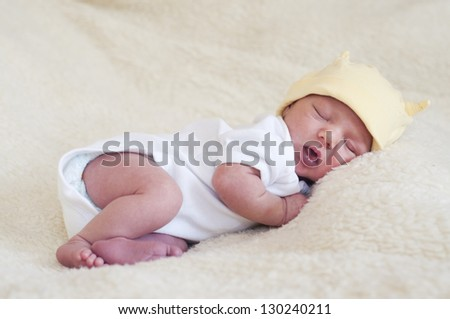 Portrait of a sleeping newborn baby; child is dressed in white vest and yellow hat and is lying on a fur blanket.