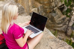 Portrait of a slender young woman on stones near sea. beautiful girl is resting on coast, enjoying outdoor recreation, holding a laptop in her hands, using Internet for business.