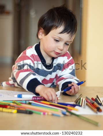 Portrait of a small child, boy or girl, drawing and playing with colorful crayons, pens and pencils.