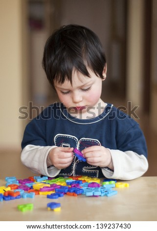 Portrait of a small child, boy or girl, playing with colorful plastic letters.