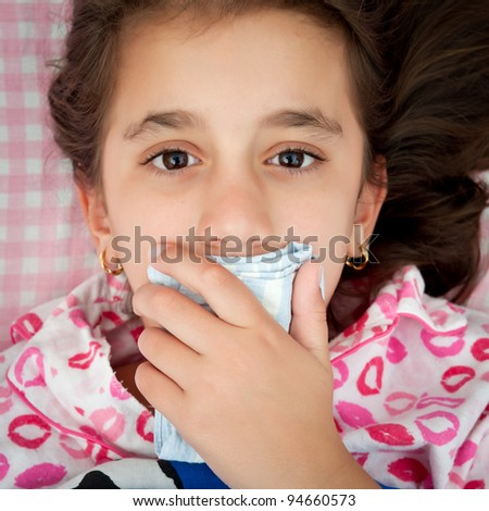 Portrait of a small girl sick with the flu covering her mouth with a handkerchief