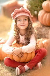 Portrait of a small village girl with pumpkins. Autumn colors.
