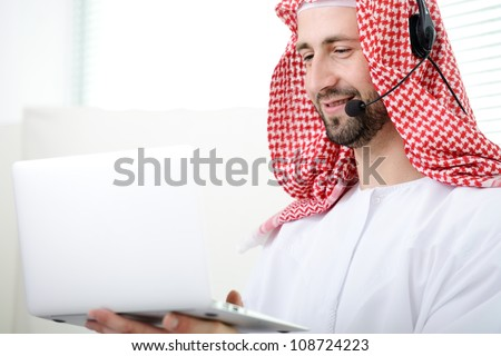 Portrait of a smart arabic business man using laptop and headset. Call center. Customer support. Helpdesk.