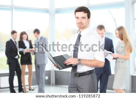 Portrait of a smart business man using laptop with colleagues in the background - stock photo