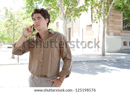 """Portrait of a smart businessman having a phone conversation on his """"smart phone"""" while standing near a classic office building in the city. - stock photo"""