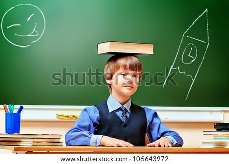 Portrait of a smart schoolboy in a classroom.