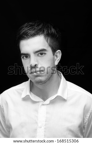 Portrait of a smart serious young man against black background