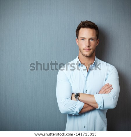 Portrait of a smart serious young man standing against blue background #141715813