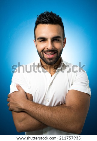 Portrait of a smart serious young man standing against blue wall