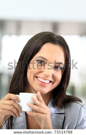 Portrait of a smart young businesswoman reading paper and drinking coffee at office