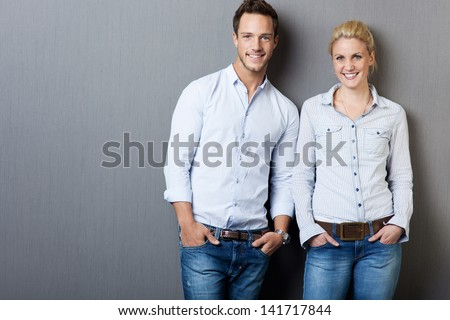Portrait of a smart young man and woman standing against gray background