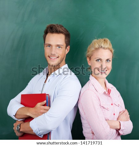 Portrait of a smart young man and woman with binder standing against chalkboard