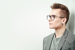 Portrait of a smart young man in a suit and glasses. Studio shot. Men's beauty.