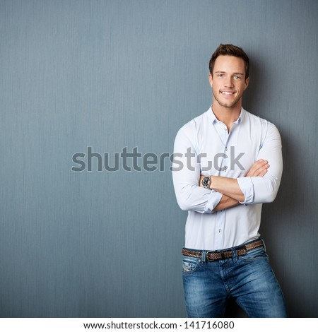 Portrait of a smart young man standing with arms crossed against gray background