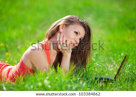 Portrait of a smart young woman lying on grass and using laptop - stock photo