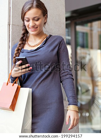 Portrait of a smart young woman shopping by an elegant store entrance in the city and using her smartphone cell during a visit to a luxurious shopping mall. Consumerism and technology, outdoors.