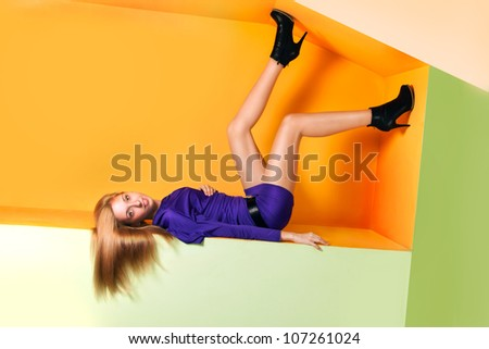 Portrait of a smiled crazy young woman lying in upside down posture