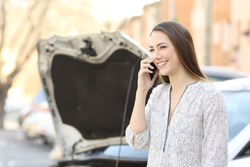 Portrait of a smiley driver calling insurance after car breakdown on the street