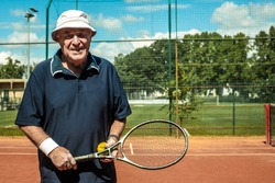 Portrait of a smiling active senior Caucasian man in sportswear, standing in a tennis court, holding tennis racket and ball