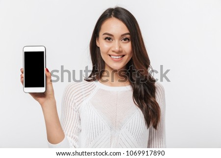 Portrait of a smiling asian businesswoman showing blank screen mobile phone isolated over white background