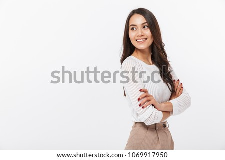 Portrait of a smiling asian businesswoman standing with arms folded and looking away isolated over white background #1069917950