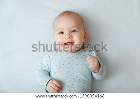 Portrait of a smiling baby in bed. Baby smiling and looking up to camera. Good morning!