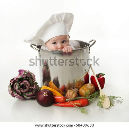 Portrait of a smiling baby sitting wearing a chef hat sitting inside a large cooking stock pot surrounded by vegetables and food, isolated on white