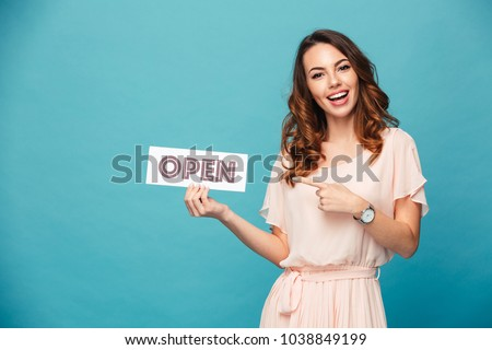 Portrait of a smiling beautiful girl wearing dress and pointing finger at an open sign isolated over blue background
